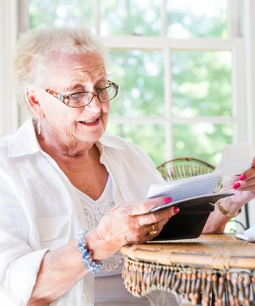 senior woman looking through the benefits of assisted living