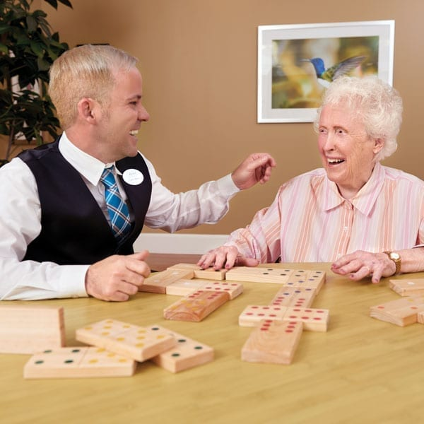 Male staff member at The Bristal plays with wooden dominoes with senior female resident.