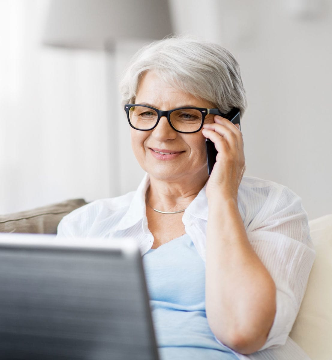 Senior woman in black glasses calls on cell phone while looking at computer.